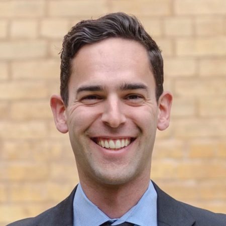 Headshot of Kyle Duarte. Kyle is an olive-skinned male with wavy brown hair. He is smiling wide and wearing a blue shirt and dark gray suit jacket. Behind him is a yellow brick wall.
